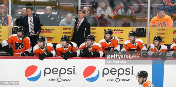Assistant Coach Kris Knoblauch and Head Coach Dave Hakstol of the Philadelphia Flyers watch the play on the ice behind Scott Laughton Valtteri...