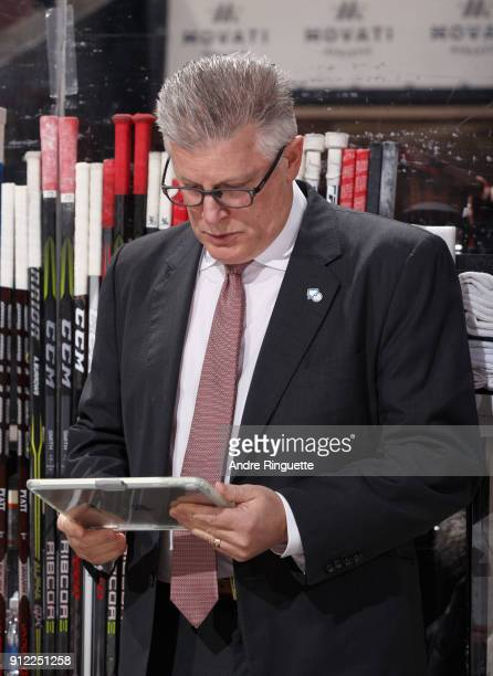 Assistant coach Marc Crawford of the Ottawa Senators works on an iPad during an NHL game against the Boston Bruins at Canadian Tire Centre on January...