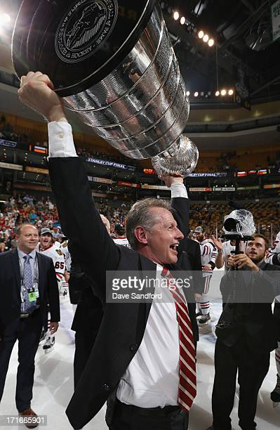 Assistant coach Mike Kitchen of the Chicago Blackhawks hoists the Stanley Cup after his team defeated the Boston Bruins 3-2 in Game Six of the 2013...