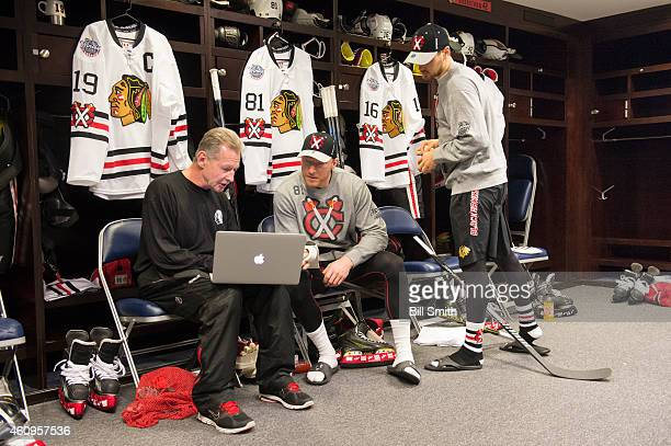 Assistant coach of the Chicago Blackhawks, Mike Kitchen, talks with Marian Hossa and Marcus Kruger prior to the NHL Winter Classic practice on...
