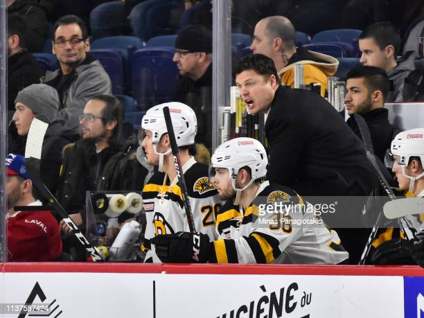 Assistant coach of the Providence Bruins Ryan Mougenel calls out instructions from behind the bench against the Laval Rocket during the AHL game at...