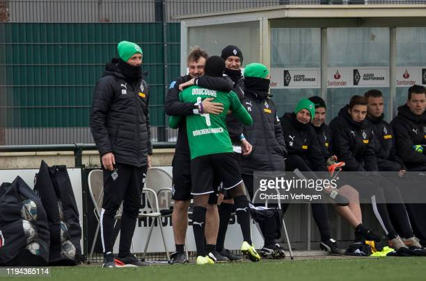 Assistant Coach Rene Maric of Borussia Moenchengladbach and Mamadou Doucoure are seen after his substation during the friendly match between Borussia...