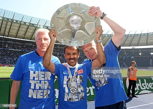 Assistant coach Rob Reekers head coach Jos Luhukay and assistant coach Markus Gellhaus of Berlin pose with the cup after winning the championship...