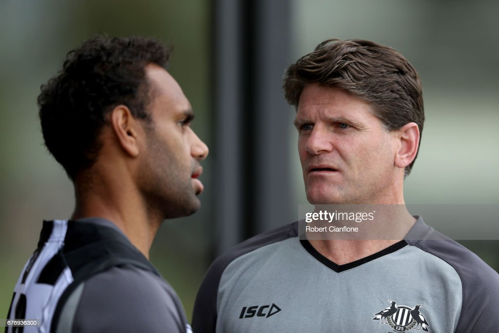 Assistant coach Robert Harvey speaks with Travis Varcoe of the Magpies during a Collingwood Magpies AFL training session at Olympic Park on May 3, 2017 in Melbourne, Australia.