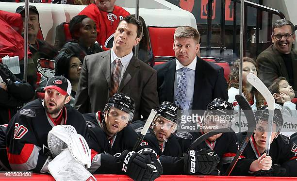 Assistant coach Rod Brind'Amour and Head Coach Bill Peters of the Carolina Hurricanes watch action on the ice as players Cam Ward Jay McClement Pat...