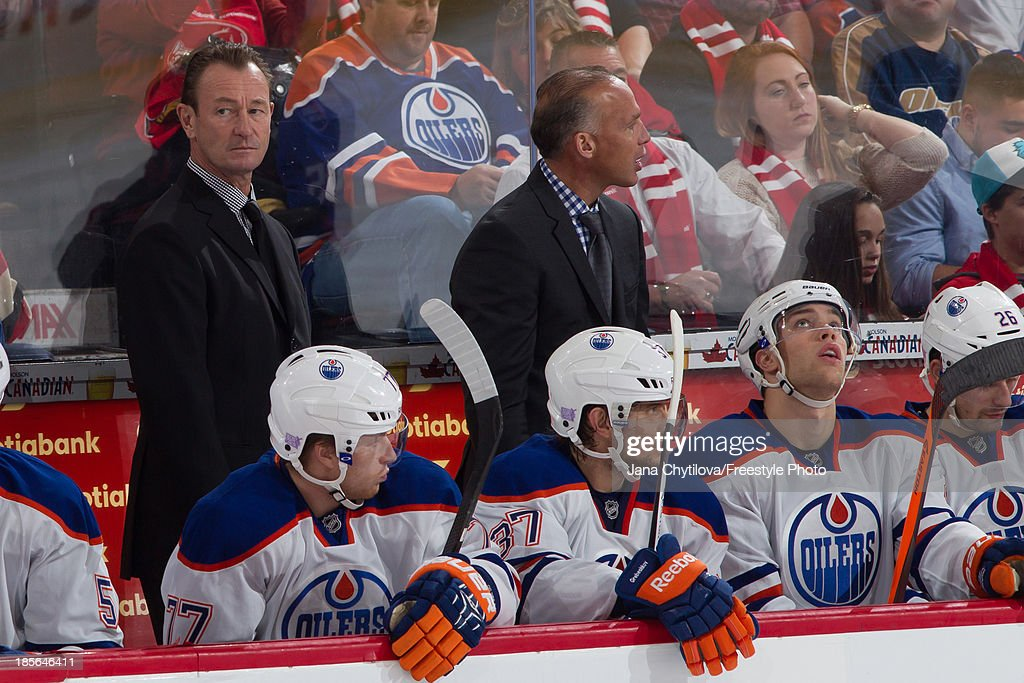 Assistant coach Steve Smith (L) of the Edmonton Oilers looks on from the bench during an NHL game against the Ottawa Senators at Canadian Tire Centre on October 19, 2013 in Ottawa, Ontario, Canada.