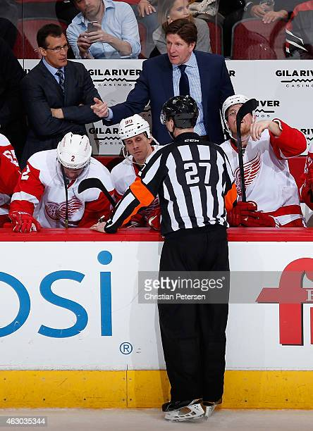 Assistant coach Tony Granato and head coach Mike Babcock of the Detroit Red Wings talk with referee Eric Furlatt during the NHL game against the...