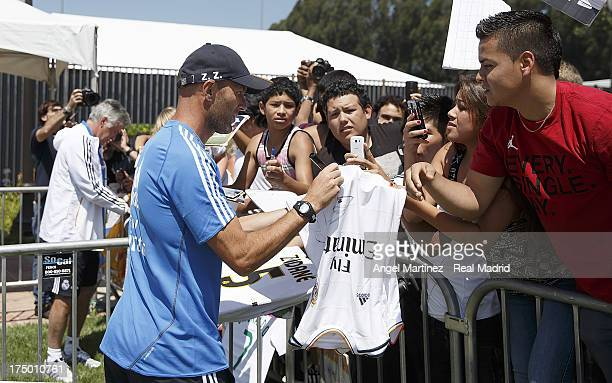 Assistant coach Zinedine Zidane and head coach Carlo Ancelotti of Real Madrid sign autographs to the fans after a training session at UCLA Campus on...