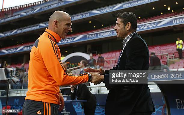 Assistant coach Zinedine Zidane of Real Madrid shakes hands with former player Fernando Hierro during a Real Madrid training session ahead of the...