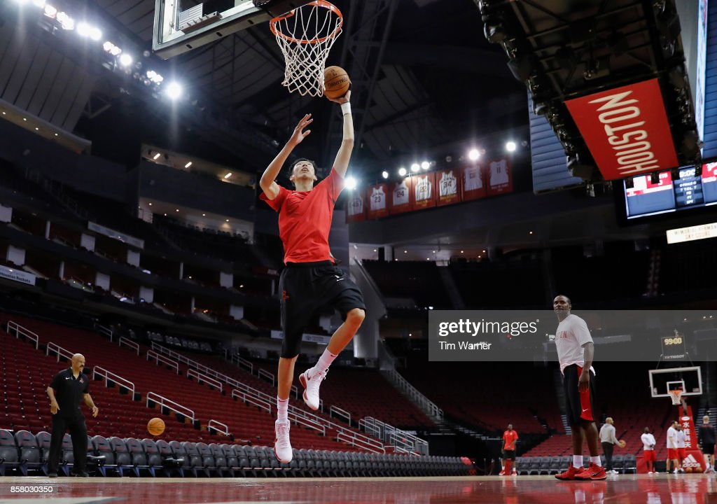 Assistant coaches John Lucas and Mike James watch as Zhou Qi #9 of Houston Rockets warms up before an exhibition game against the Shanghai Sharks at Toyota Center on October 5, 2017 in Houston, Texas.