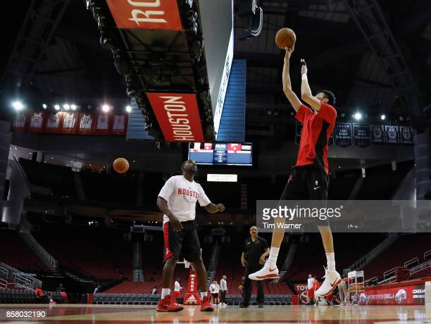 Assistant coaches Mike James and John Lucas watch Zhou Qi of Houston Rockets warm up before an exhibition game against the Shanghai Sharks at Toyota...