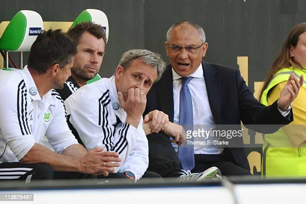 Assistant coaches Werner Leuthard, Bernd Hollerbach, Pierre Littbarski and head coach Felix Magath react during the Bundesliga match between VfL...