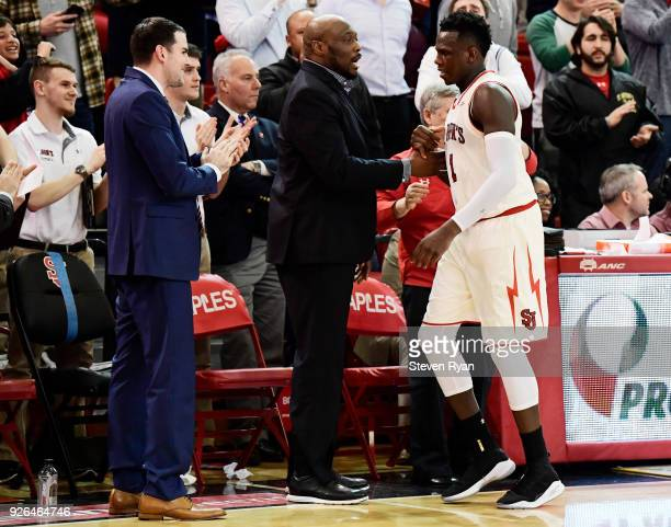 Assistant coachs Greg St Jean and Mitch Richmond congratulate Bashir Ahmed of the St John's Red Storm after he comes out of the game against the...
