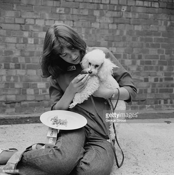 A assistant Hazel Fisher at London Airport with the poodle 'Pipper' who will only eat chow mein London 27th July 1967