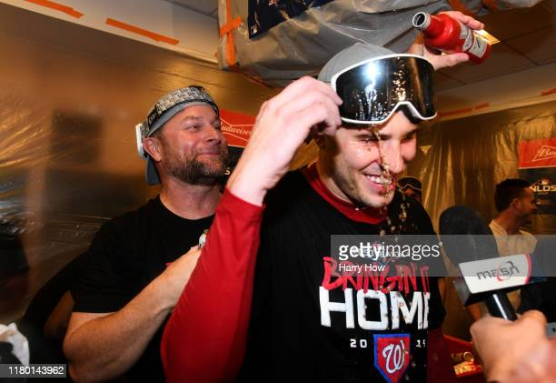 Assistant hitting coach Joe Dillon and pitcher Patrick Corbin of the Washington Nationals celebrate in the locker room after their team defeated the...