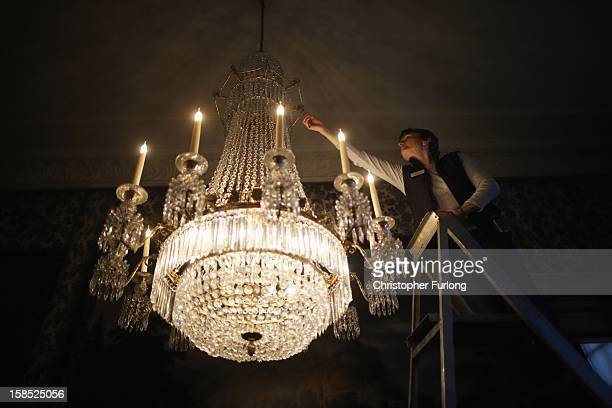 Assistant House Keeper at Chatsworth House Janet Bitton deep cleans a regency cut glass chandlier at the stately home on December 18 2012 in...