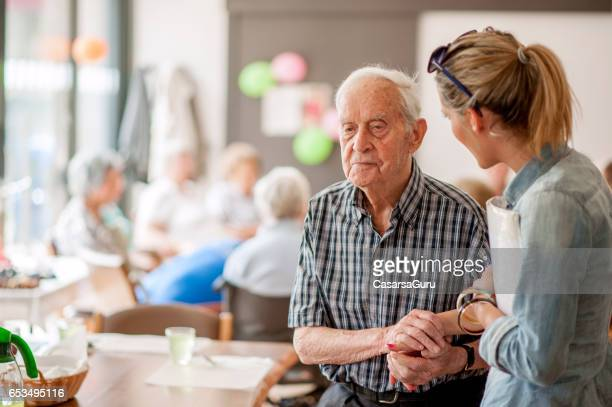 assistant in the community center giving advice to a senior man - community centre stock pictures, royalty-free photos & images