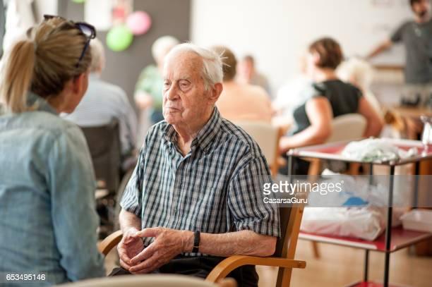 Adjoint au centre communautaire donnant des conseils à un homme Senior