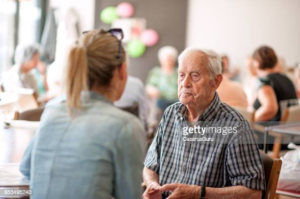 Assistent im Gemeindezentrum Beratung zu einem älteren Mann