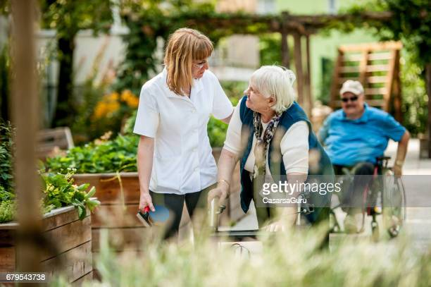 assistant in the retirement community have a walk with the senior woman - residential care stock photos and pictures