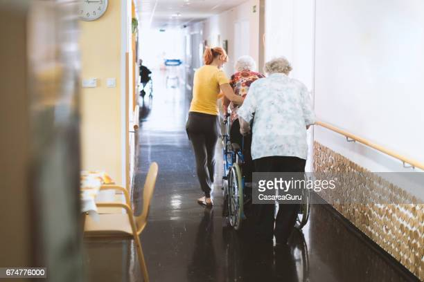 Assistant In The Retirement Community Helping Senior Woman Walking