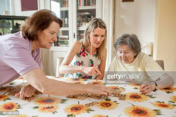 assistant in the retirement community playing domino with senior women - residential care stock photos and pictures