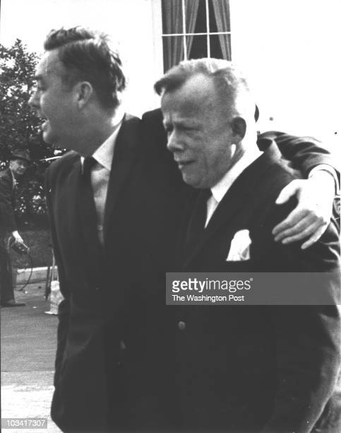 Assistant Labor Secretary Daniel Patrick Moynihan and artist William Walton leave the White House after learning that President John Kennedy had died...