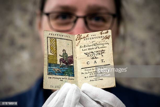 Assistant librarian Ann Martin poses for a photograph with a small book entitled 'The Adventures of Sir Richard Whittington Lord Mayor of London and...