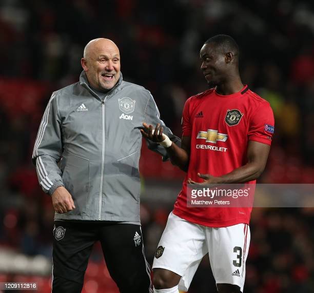 Assistant Manager Mike Phelan and Eric Bailly of Manchester United walk off after the UEFA Europa League round of 32 second leg match between...