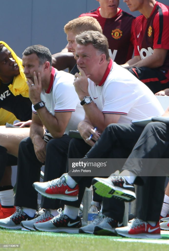 Assistant Manager Ryan Giggs and Manager Louis van Gaal of Manchester United watch from the bench during the pre-season friendly match between Manchester United and AS Roma at Sports Authority Field at Mile High on July 26, 2014 in Denver, Colorado.