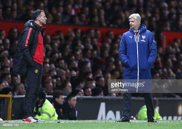 Assistant Manager Ryan Giggs of Manchester United and Manager Arsene Wenger of Arsenal watch from the touchline during the FA Cup Quarter Final match...