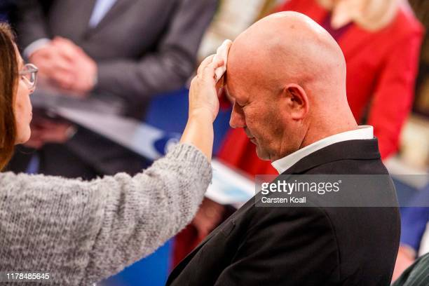 TV assistant powders Thomas Kemmerich lead candidate of the German Free Democrats before a television interview following state elections in...