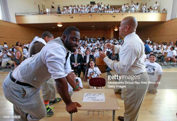 Assistant principal Marcel Baker right challenges Raider's defensive end Justin Tuck to an arm wrestling contest during the assembly at Alliance...