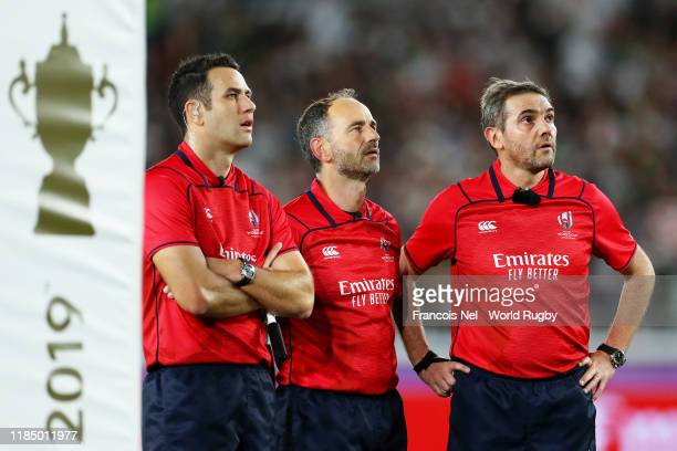 Assistant referee Ben O'keefe, Romain Poite and referee Jerome Garces await a decision for the first try from the TMO during the Rugby World Cup 2019...