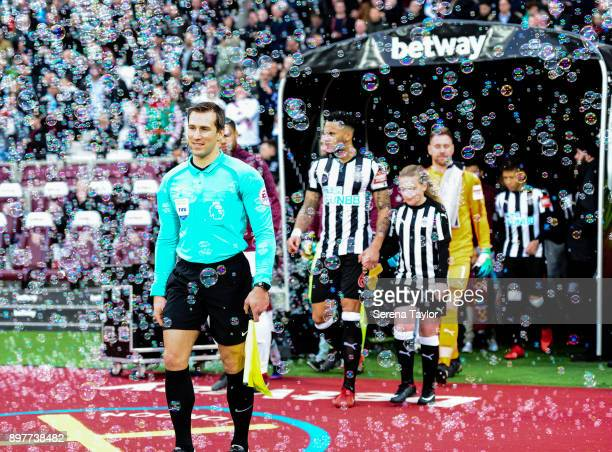 Assistant Referee Constantine Hatzidakis walks out of the tunnel with bubbles floating around them during the Premier League match between West Ham...