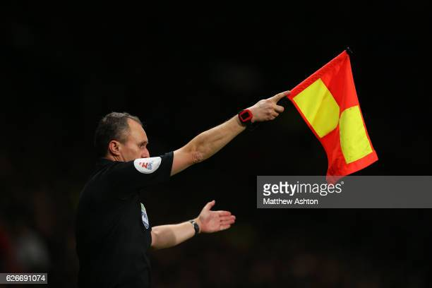 Assistant Referee Darren Cann with the Goalline technology watch on his arm holding up the yellow and red flag for an offside decision