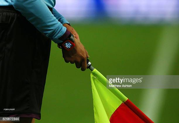 Assistant referee / linesman holding his flag to award offside - wearing a watch showing the time played during a game which through a vibrating...