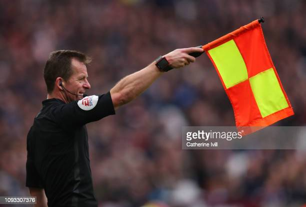 Assistant referee Marc Perry holds up the flag for offside during the Premier League match between West Ham United and Arsenal FC at London Stadium...