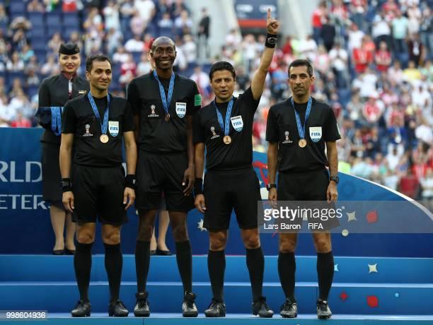 Assistant referee Mohammadreza Mansouri Fourth official Malang Diedhiou Referee Alireza Faghani and Assistant referee Reza Sokhandan pose with medals...