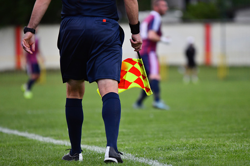 Assistant referee or Lineman of football or soccer holding flag 1150325735