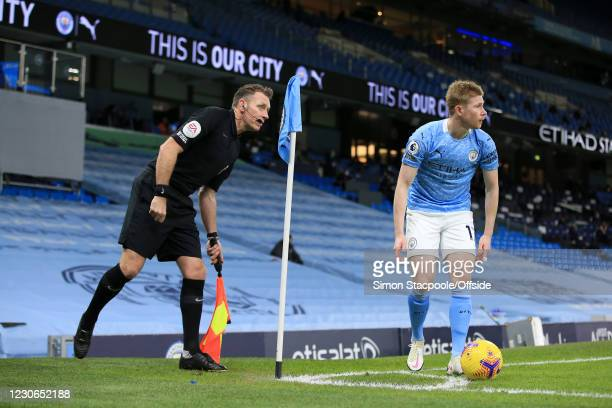 Assistant referee Scott Ledger looks on as Kevin de Bruyne of Manchester City prepares to take a corner during the Premier League match between...