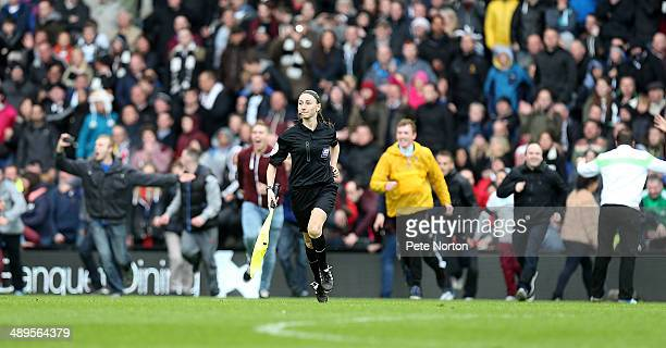 Assistant Referee Siam Massey runs to the safety of the changing rooms as Derby County fans invade the pitch to celebrate at the final whistle during...