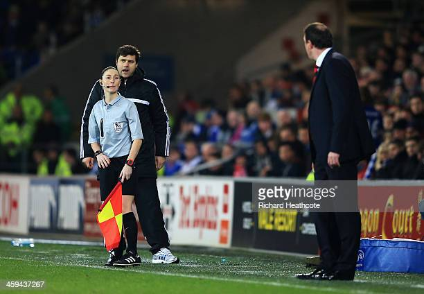 Assistant referee Sian Massey talks to Malky Mackay, manager of Cardiff City watched by Mauricio Pochettino, manager of Southampton during the...