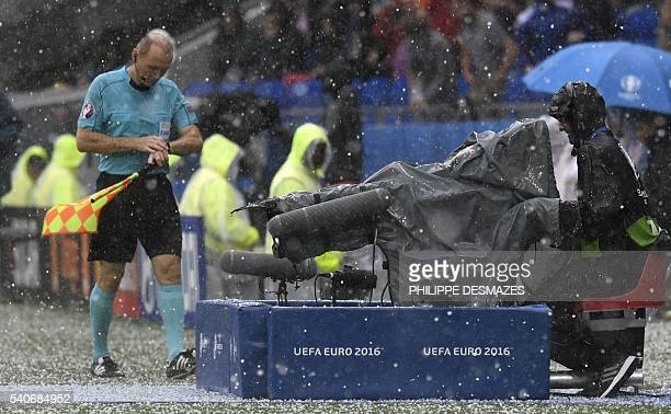 Assistant referee Slovakian Roman Slysko leaves the pitch during a hailstorm during the Euro 2016 group C football match between Ukraine and Northern...