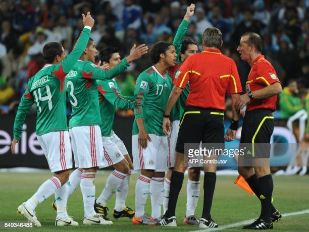Assistant referee Stefano Ayroldi Italian referee Roberto Rosetti speak to Mexico's players who argue that a goal by Argentina's striker Carlos Tevez...