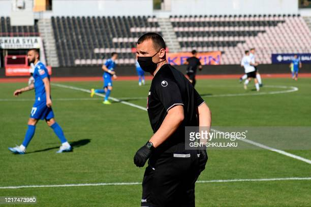 Assistant referee wearing a protective face mask attends the Albanian Superleague football match between KF Kukesi and FC Luftetari at the empty...