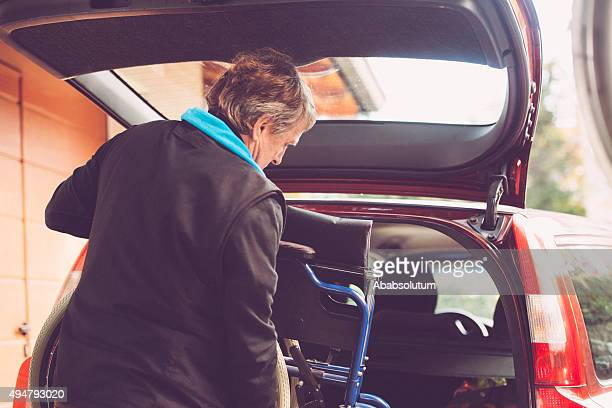 Assistant Son Putting Wheelchair to the Car, Europe