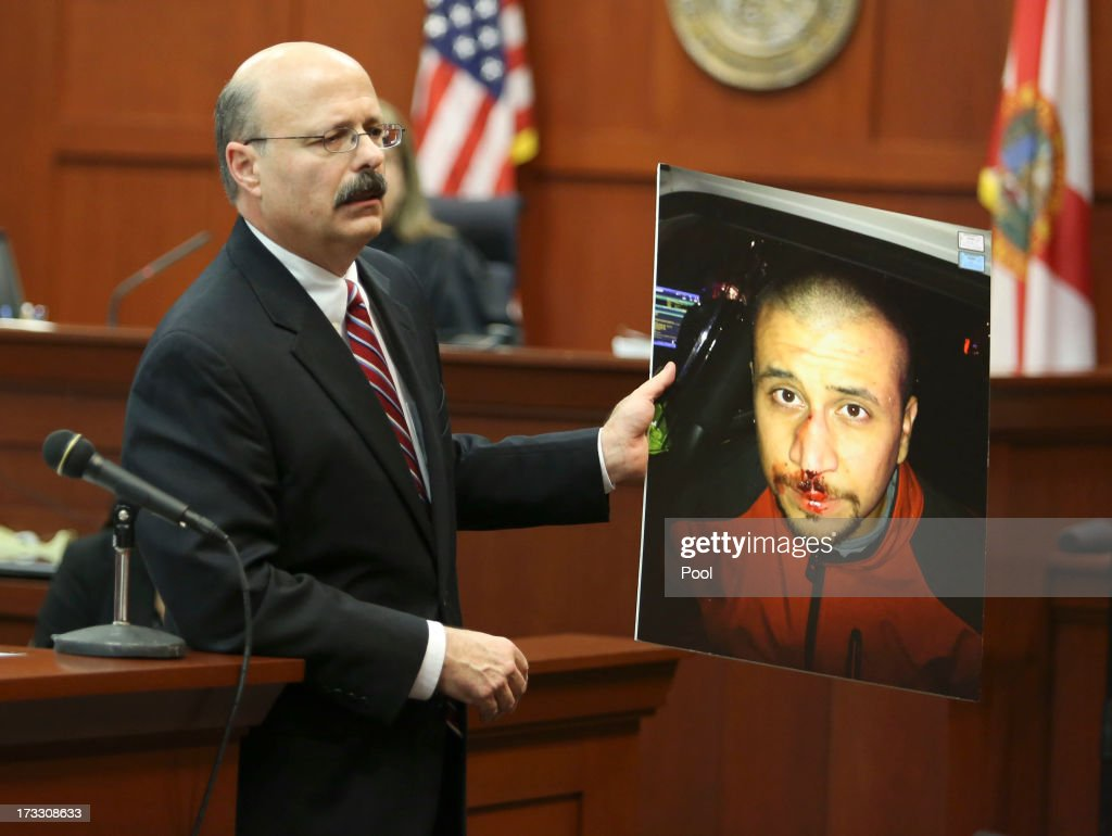 Assistant state attorney Bernie de la Rionda shows a picture of George Zimmerman to the jury while presenting the state's closing arguments against George Zimmerman during his murder trial in Semimole circuit court July 11, 2013 in Sanford, Florida. Judge Debra Nelson has ruled that the jury can also consider a manslaughter charge along with the second-degree murder charge in the shooting death of Trayvon Martin.