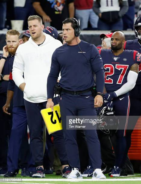Assistant strength and conditioning coach Brian Cushing of the Houston Texans and J.J. Watt stand on the sideline in the fourth quarter against the...