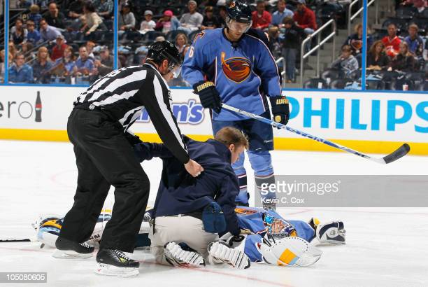 Assistant trainer Step Roberts attends to goaltender Ondrej Pavelec of the Atlanta Thrashers after he fell backwards on the ice in the first few...